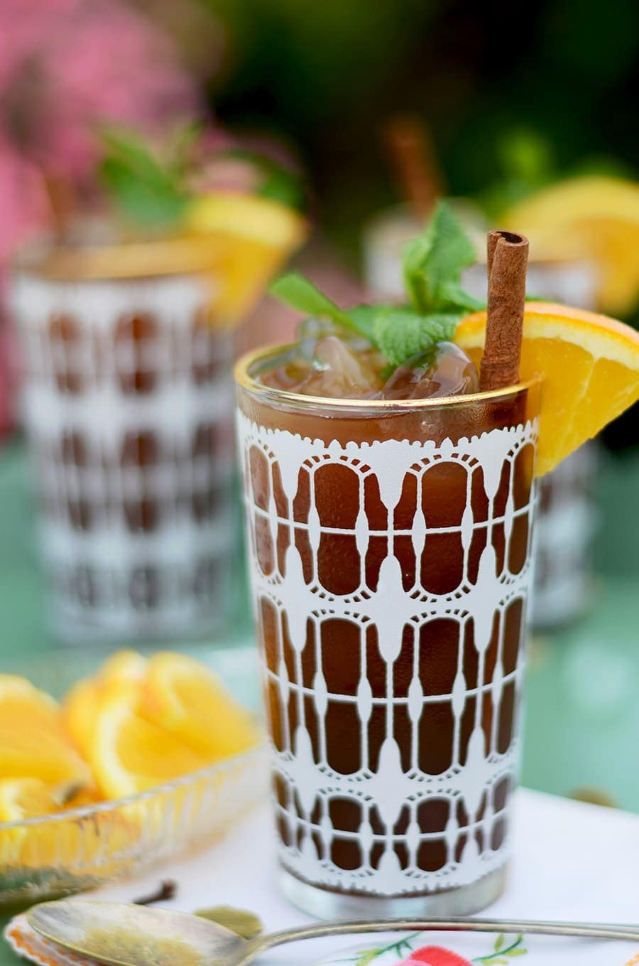 closeup of chai iced tea in a vintage glass with a white pattern and gold rim