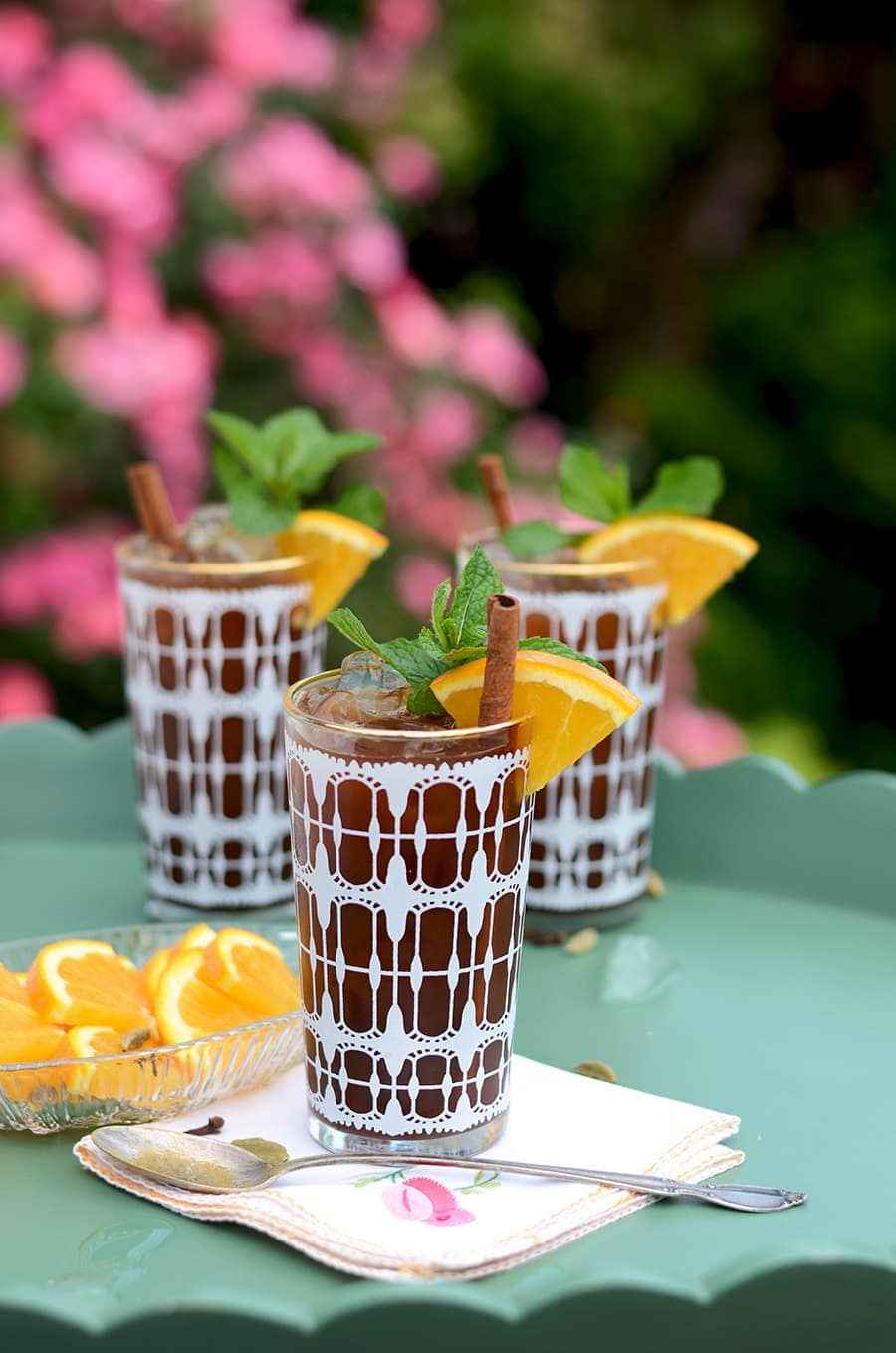 Vintage glasses filled with chai iced tea and garnished with oranges, fresh mint and cinnamon sticks