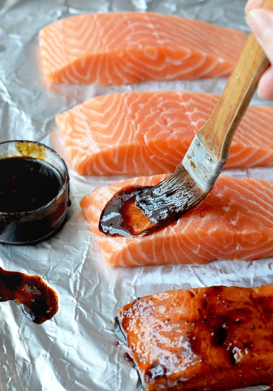 Salmon on foil being basted with sesame ginger glaze