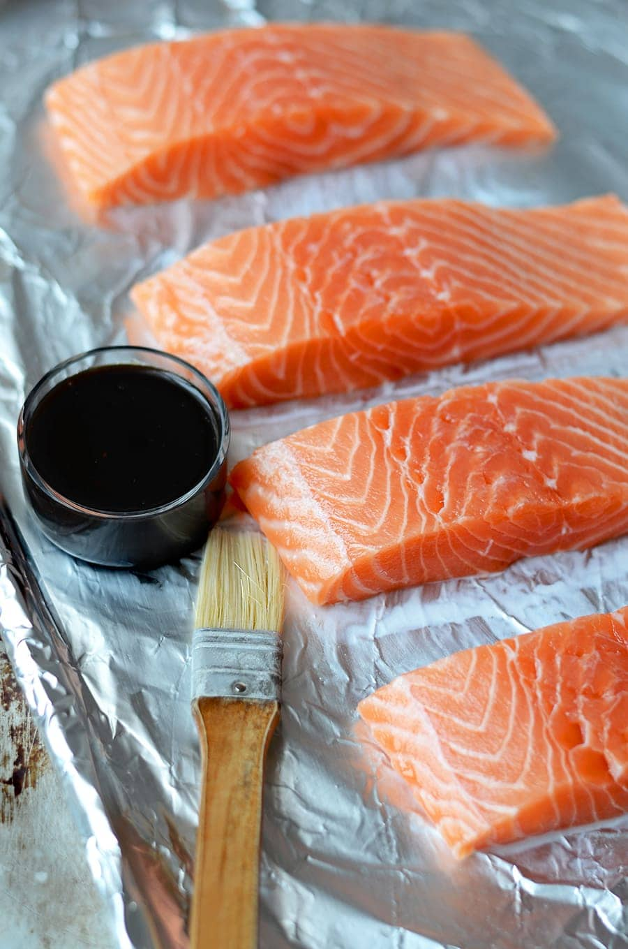 Salmon on foil next to a cup of sesame ginger glaze and a basting brush