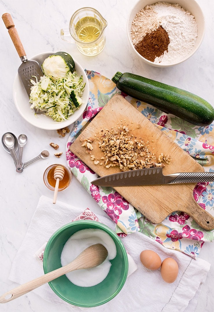 ingredients for zucchini bread: honey, flour, spices, sugar, walnuts grated zucchini, vegetable oil, eggs
