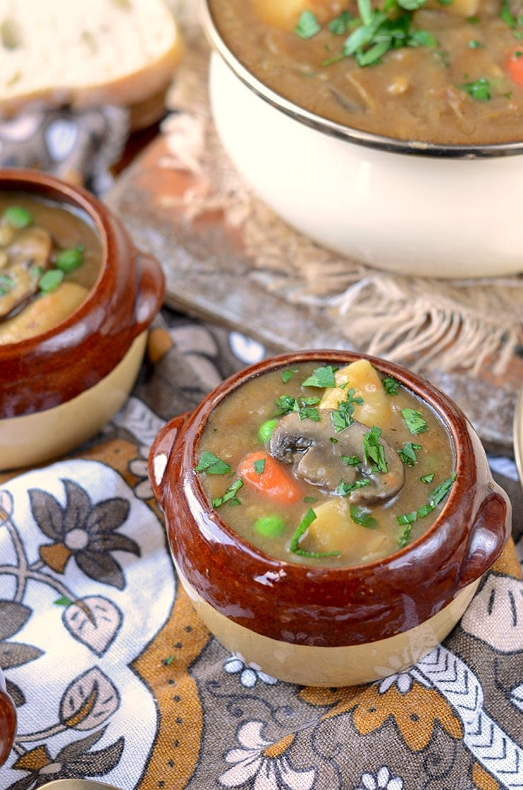 mushroom floating on top of a crock of guinness stew