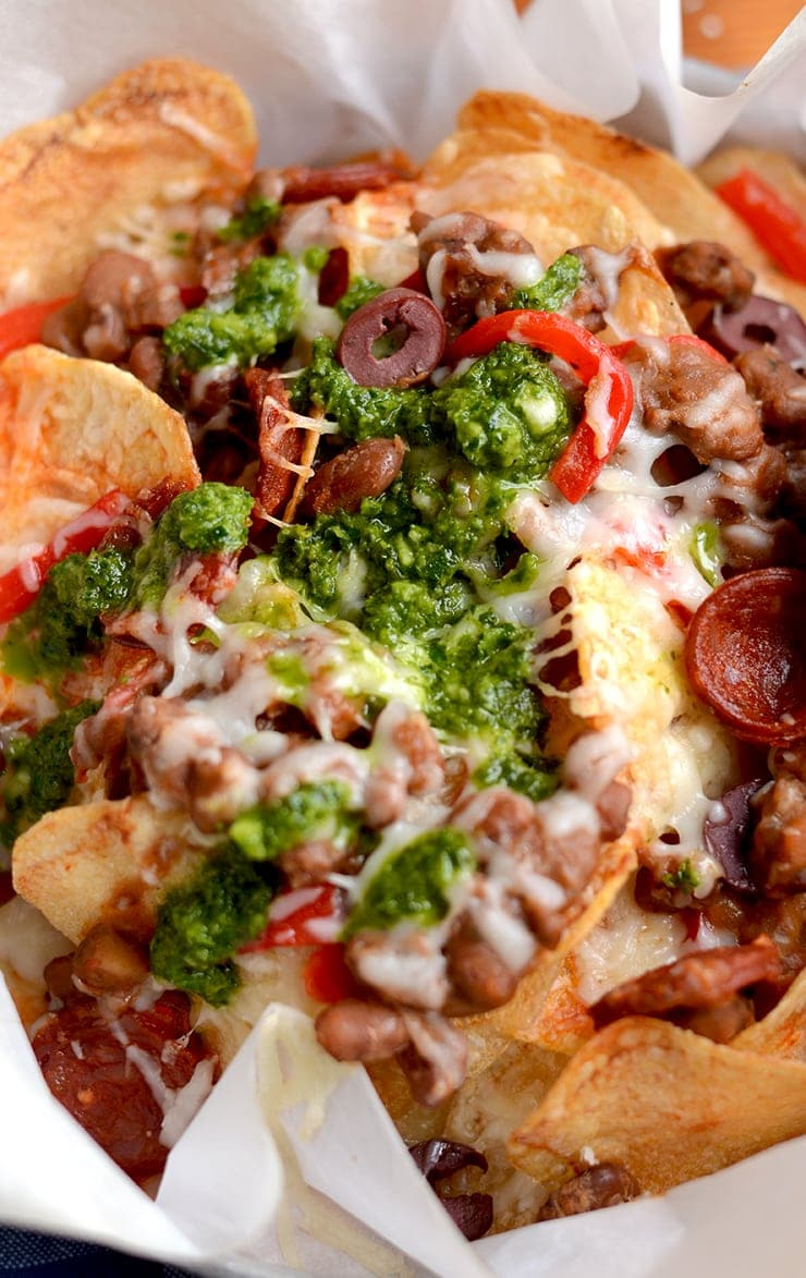 Homemade potato chips get loaded with savory ingredients in this Spanish Potato Nachos recipe. Far from ordinary, these nachos are topped with Manchego cheese, Chorizo sausage and served with a fresh, zesty Chimichurri. | vintagekitty.com