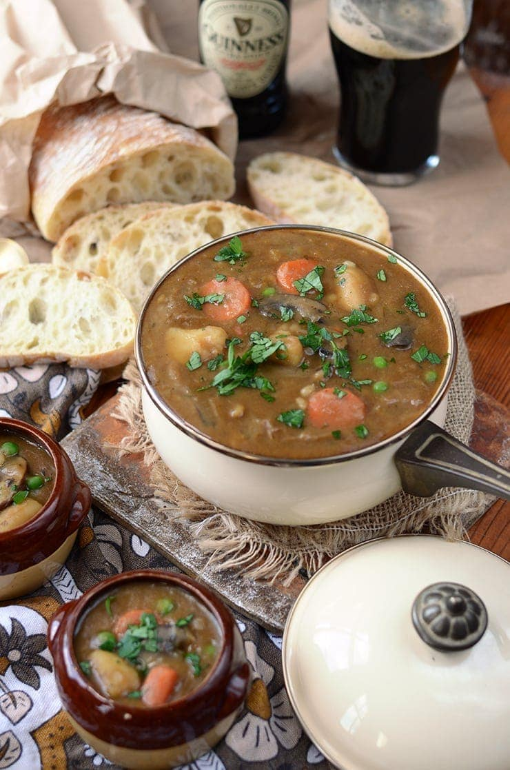 Vegan guinness stew in an enamel pot surrounded by bread and a glass of beer