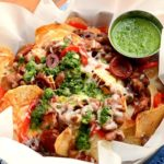 Homemade potato chips get loaded with savory Spanish ingredients in this fusion recipe. Far from ordinary, these nachos are topped with Manchego cheese, Chorizo sausage and served with a fresh, zesty Chimichurri. | vintagekitty.com
