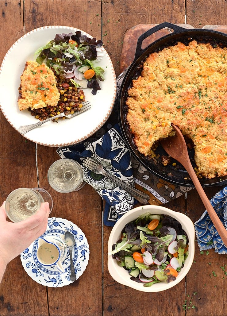 Wooden table set with barbecue lentil casserole and salad