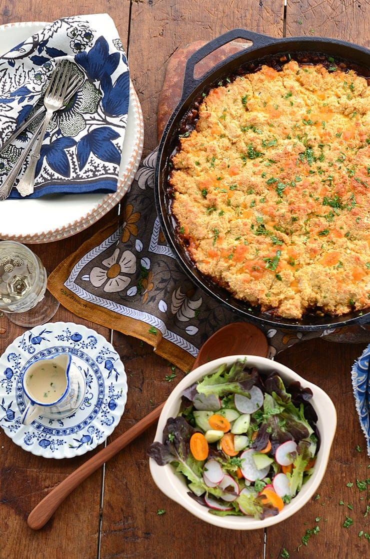 cast iron skillet with baked lentils with cornmeal biscuit topping