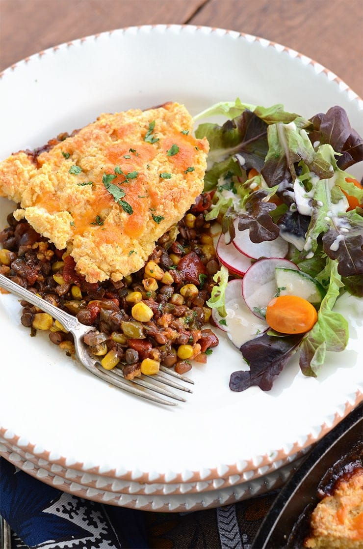 closeup of baked lentils with cheddar cornmeal biscuit topping on a pottery plate
