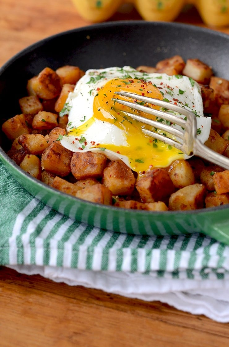 Breakfast Potatoes in Skillet topped with Runny Sunny Side Up Egg