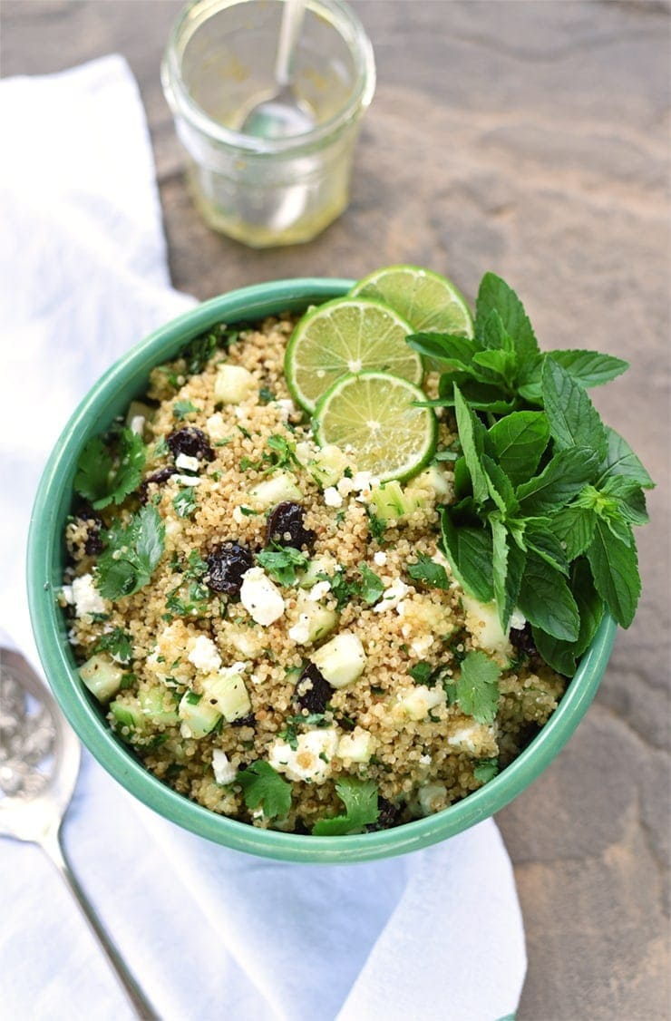 top down view of quinoa salad in a green bowl garnished with limes and mint leaves