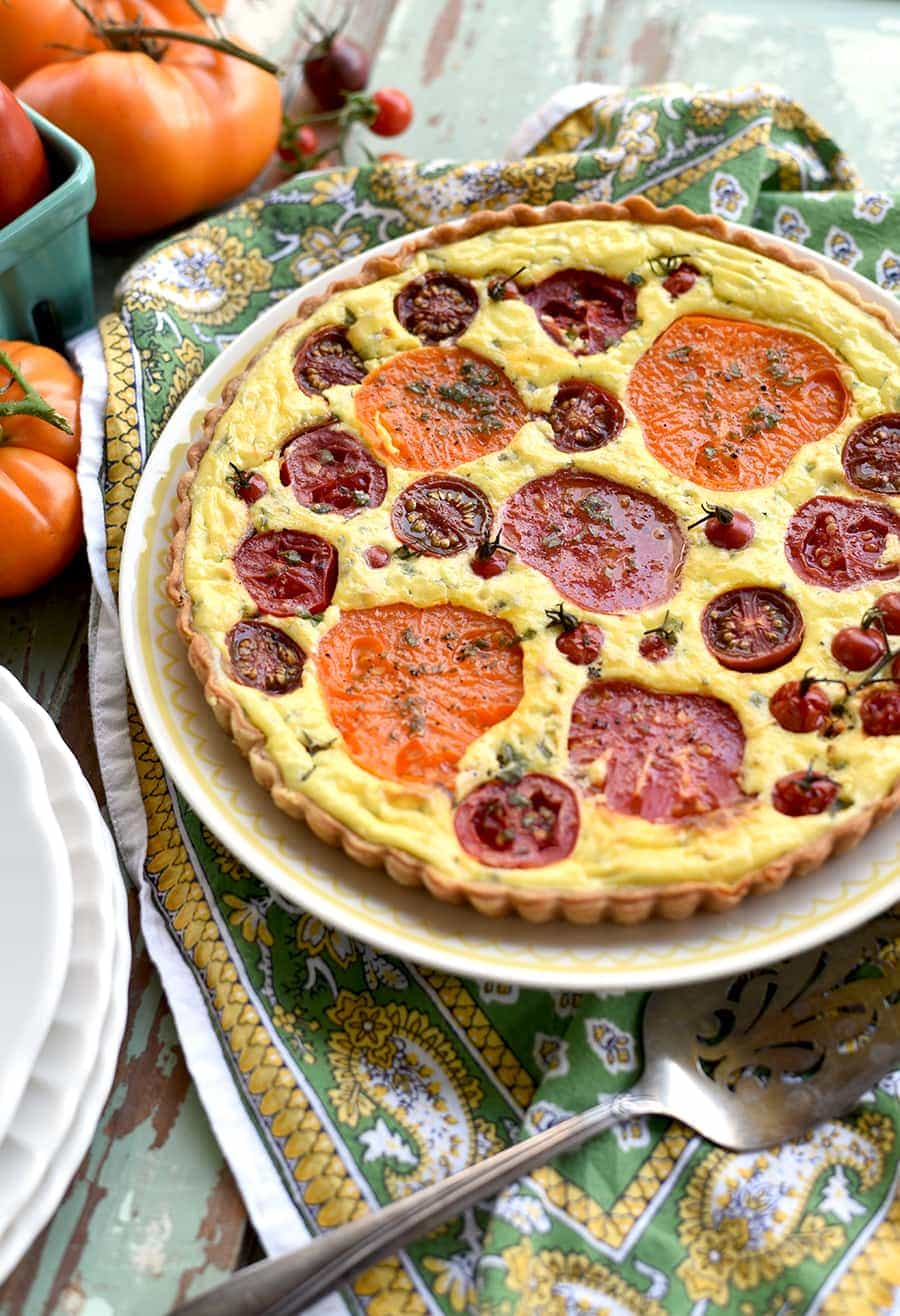plate with tart filled with heirloom tomatoes on a french paisley green napkin