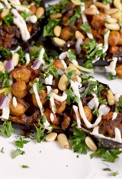 Roasted eggplant gets stuffed with warmly spiced chickpeas and carrots in this lavish vegan recipe. Finally it's drizzled with a sweet lemon tahini dressing.