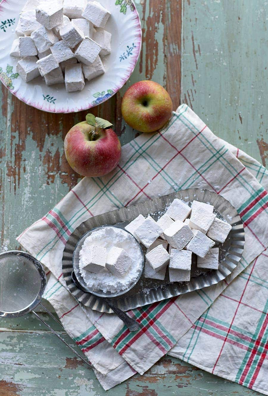 Dredging caramel apple marshmallows in powdered sugar
