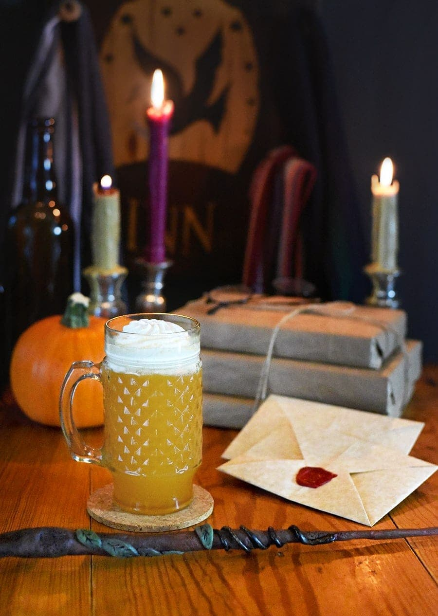 Mug of butterbeer cocktail on a wooden table next to a wand with candles and sealed letters in the background