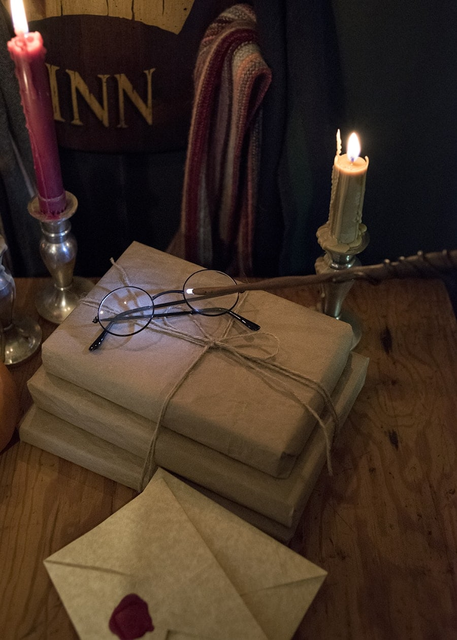 Handmade Harry Potter inspired wand with a glowing tip lighting up Harry Potter glasses resting on wrapped books in front of burning candles.