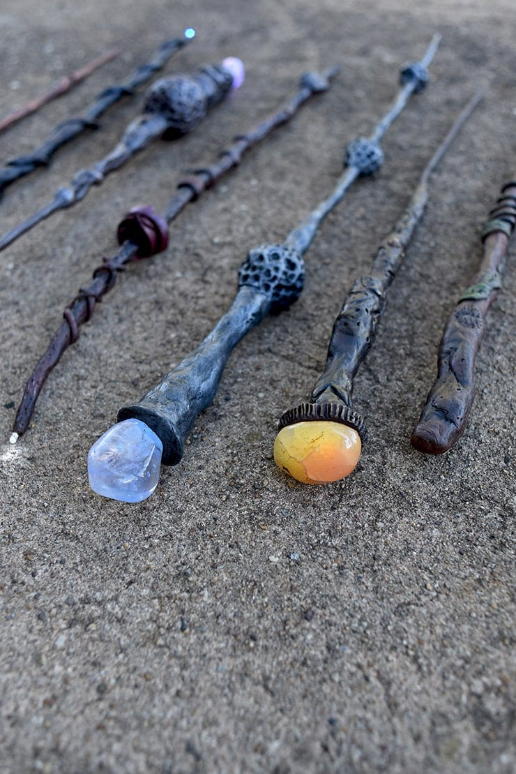 Seven hand made light up Harry Potter inspired wands laid out on pavement. Several have glowing tips or gems on the back.