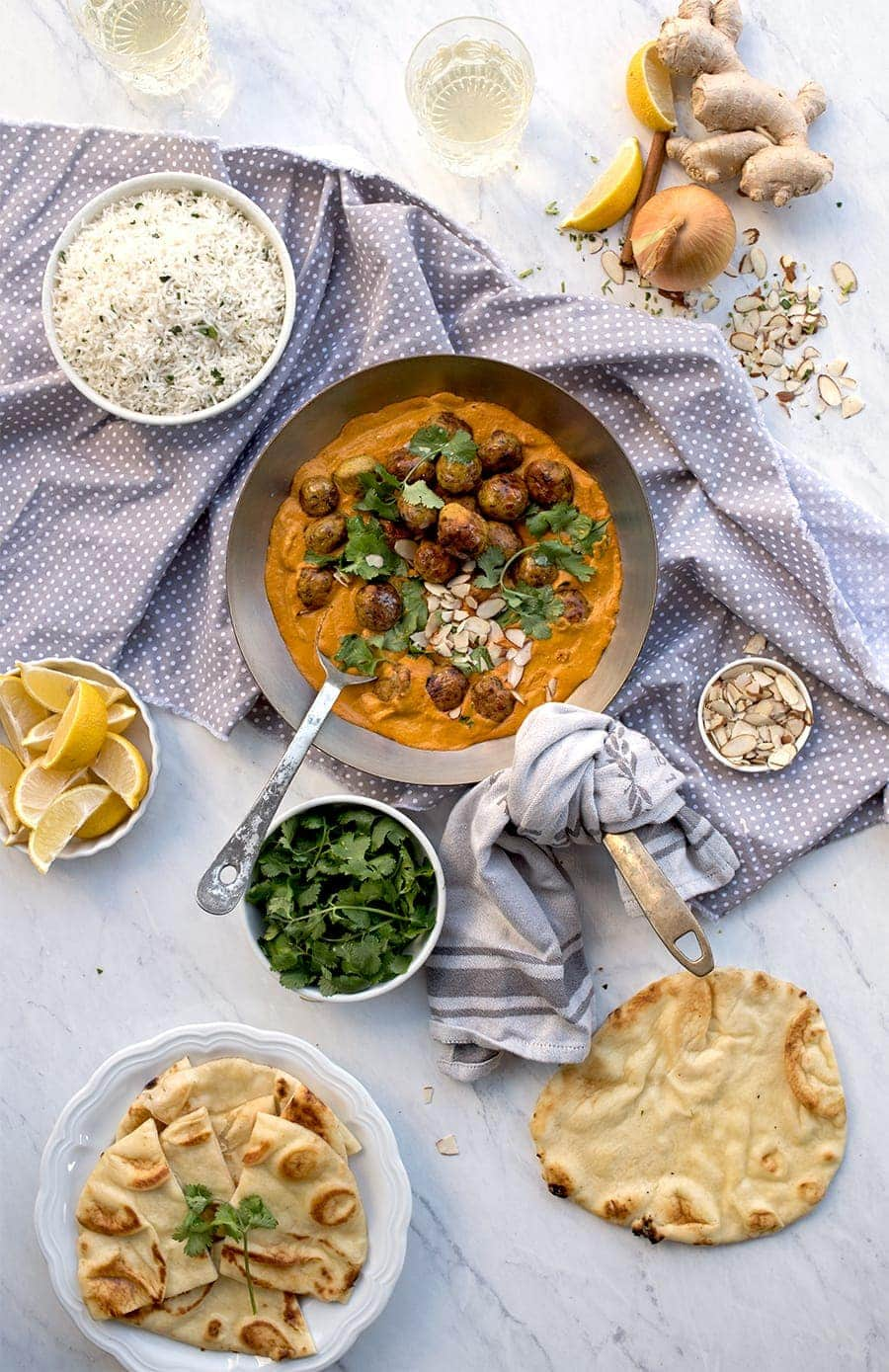 Table with skillet of butter chicken, naan and rice