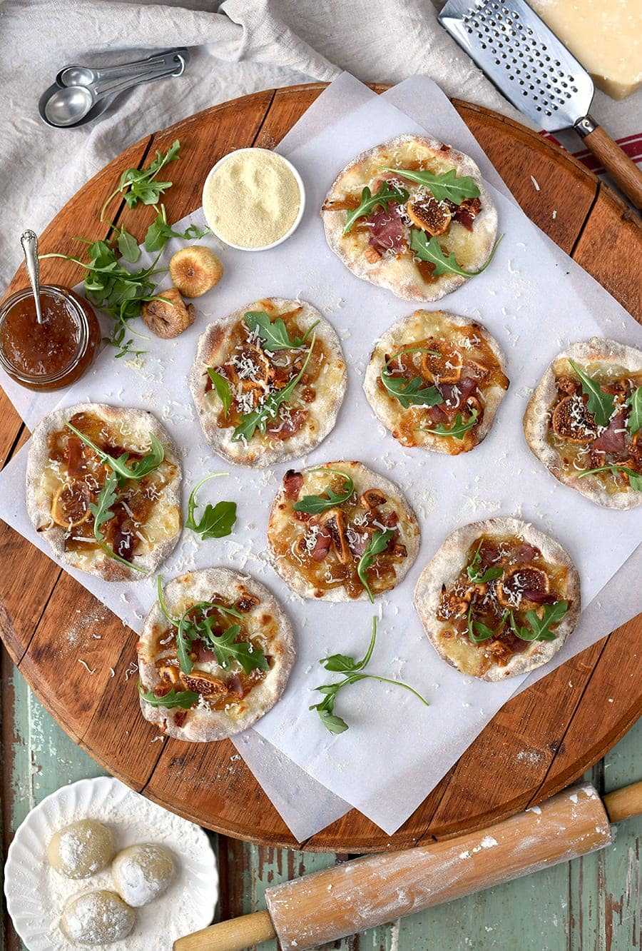These delicious mini fig pizzas are a casual appetizer with tons of foodie appeal! Dried figs make this pizza recipe a winter staple. Prosciutto, caramelized onions and arugula top fresh mozzarella for a sweet and savory pie that's hard to resist! #pizza #appetizers #gameday #prosciutto #caramelizedonions
