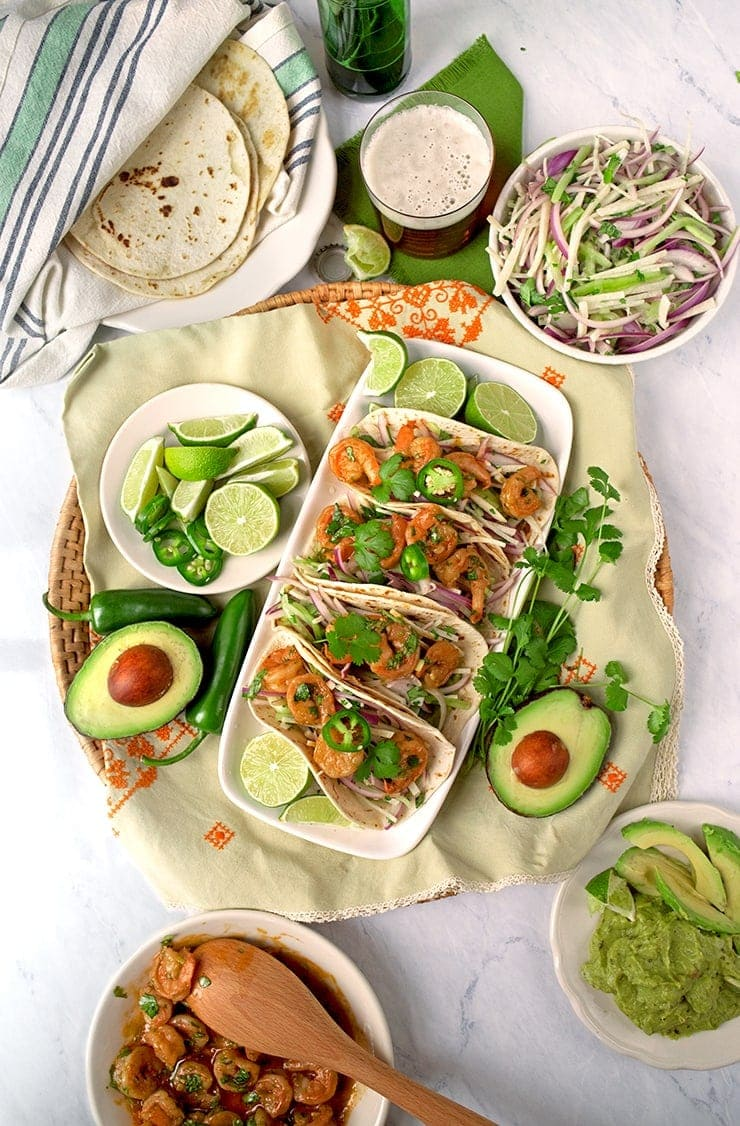 These 30-minute Tequila Shrimp Tacos are paired with a quick slaw that will brighten up your dinner routine. #shrimptacos #jicama #30minutemeal #easydinner