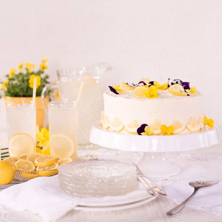 Lemon Blueberry Cake on cake plate next to lemonade and flowers