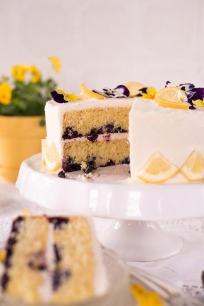 cake decorated with lemons and pansies on a white cake pedestal next to lemonade and a pot of flowers