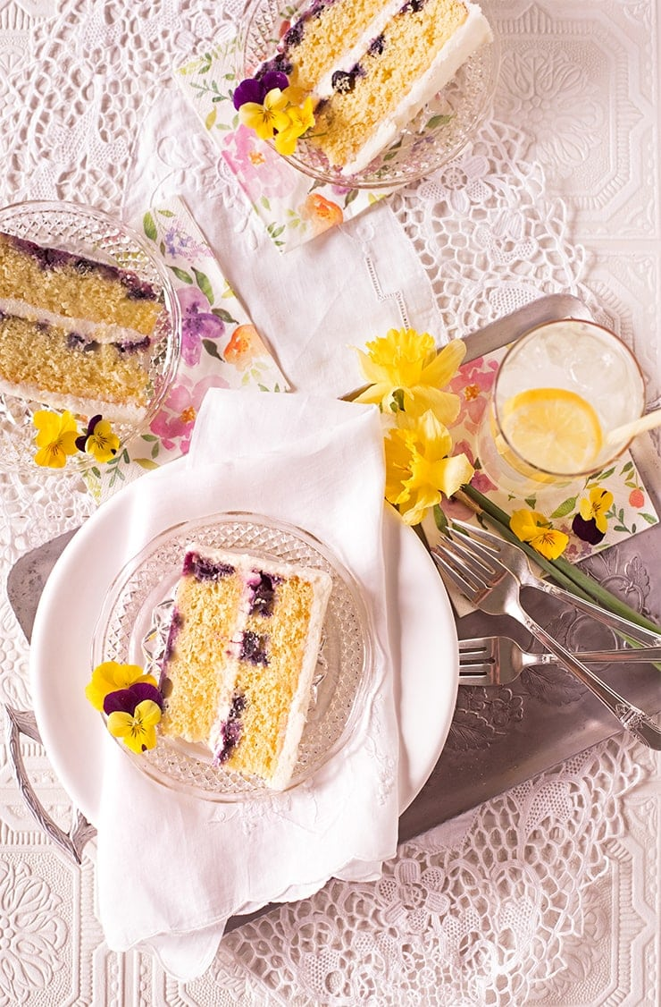 This light and lemony cake is a warm weather delight. It's bright citrus flavors are punctuated by sweet blueberries and tangy cream cheese frosting. It's made from scratch using lemon zest and champagne! #lemoncake #scratchcake #blueberry