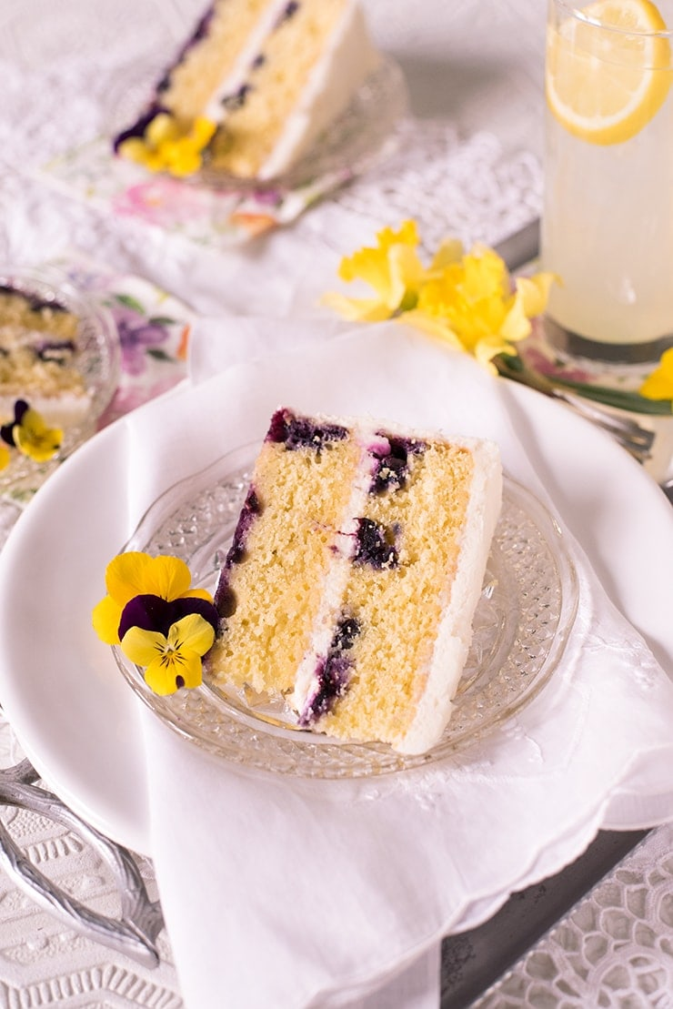 This light and lemony cake is a warm weather delight. It's bright citrus flavors are punctuated by sweet blueberries and tangy cream cheese frosting. It's made from scratch using lemon zest and champagne! #lemoncake #scratchcake #blueberry #lemonblueberrycake