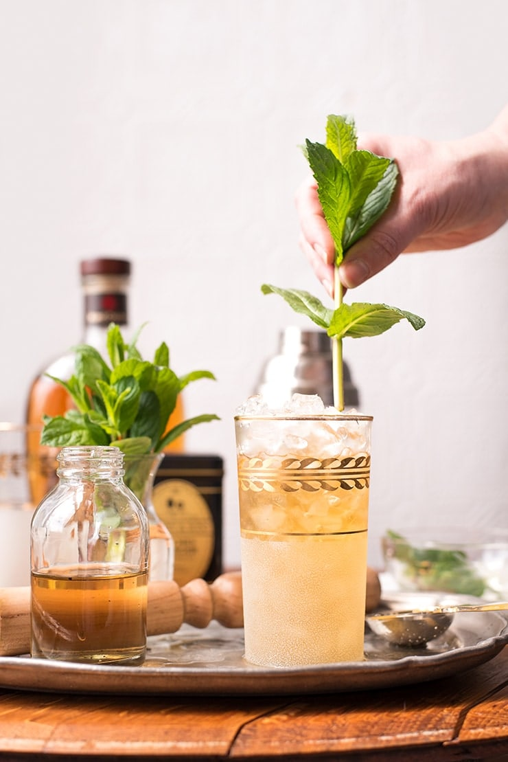 hand placing a spring of mint in a mint julep