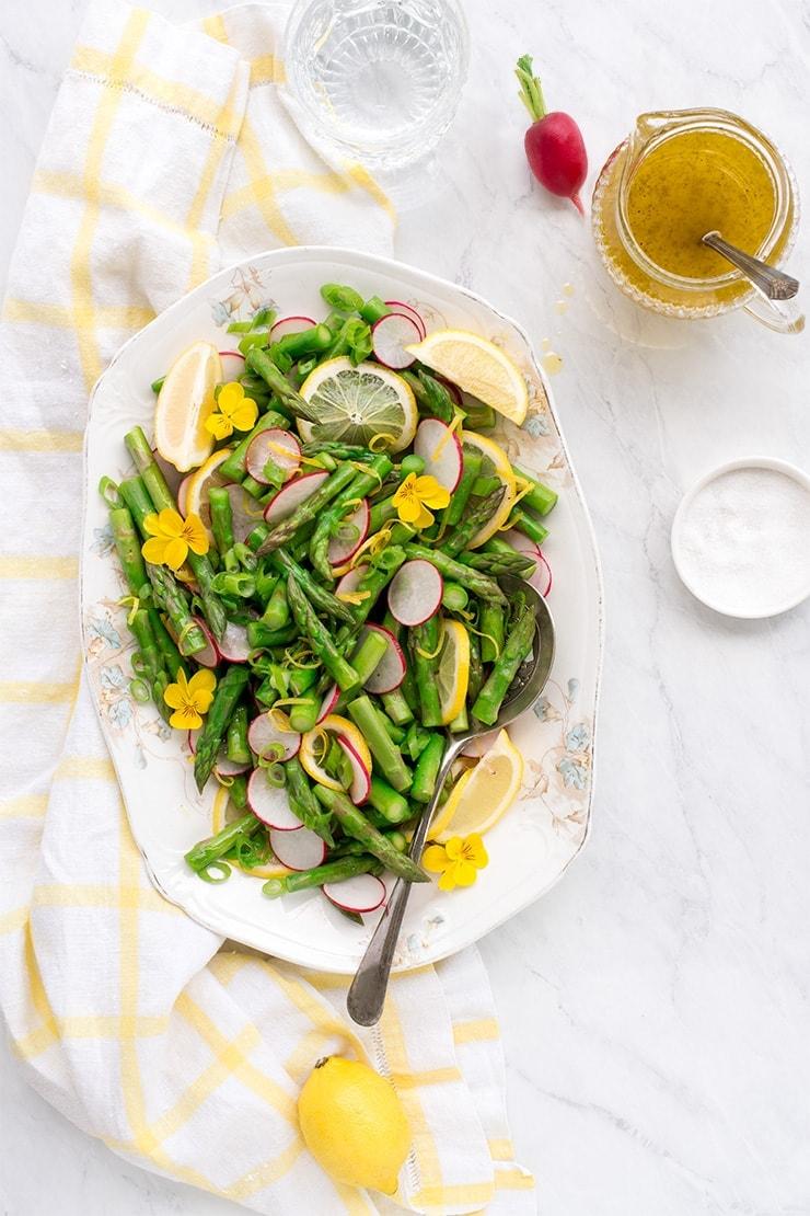 asparagus salad on an antique platter next to pitcher of lemon vinaigrette