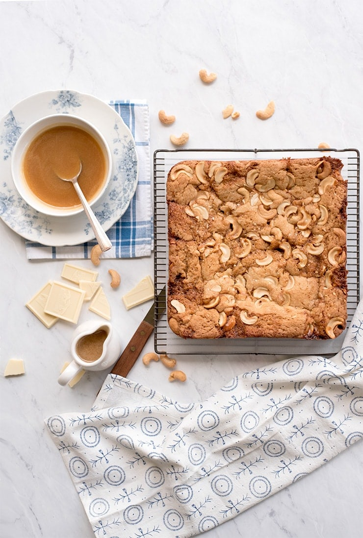 cashew blondies on a cooling rack next to a bowl of salted caramel