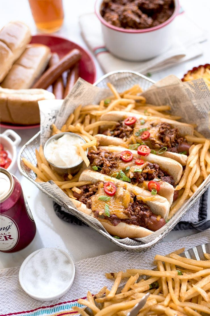 chili cheese dogs in a basket with fries