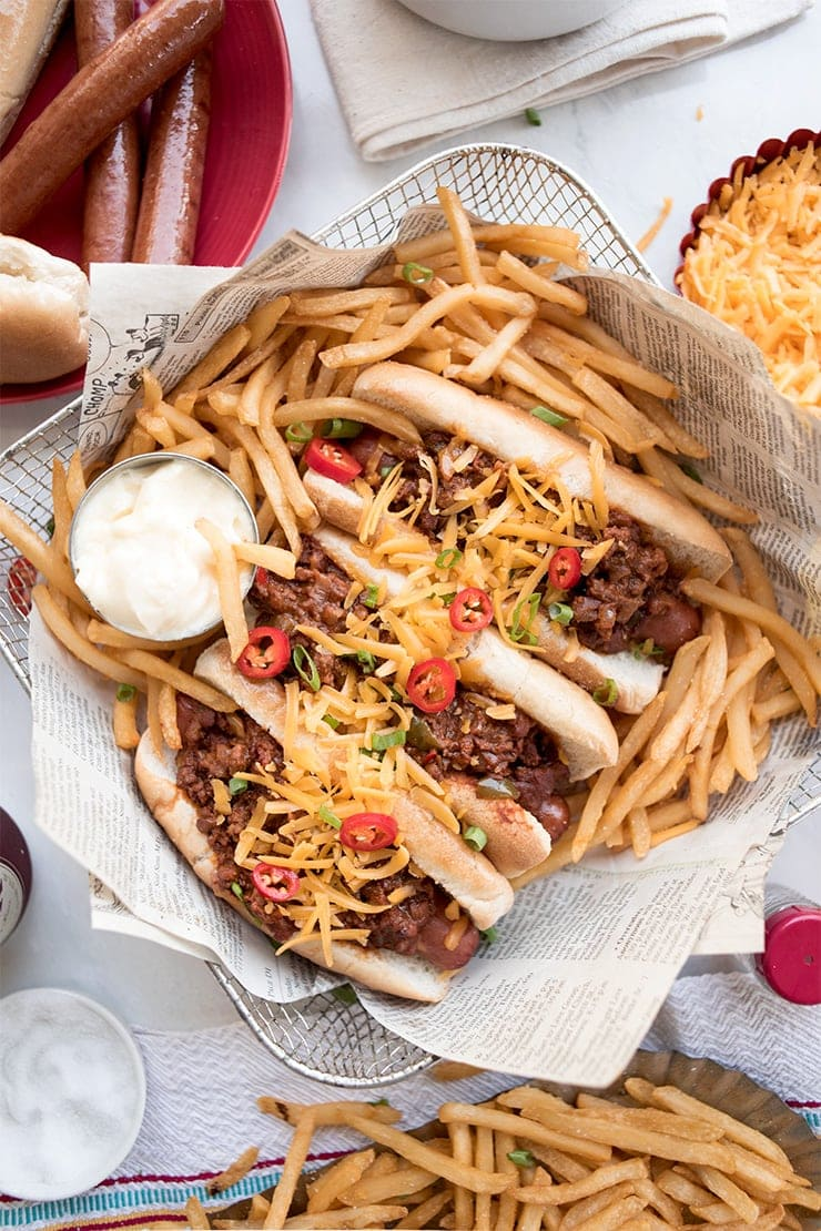 close up of chili cheese hotdogs in a basket lined with newspaper and surrounded by french fries
