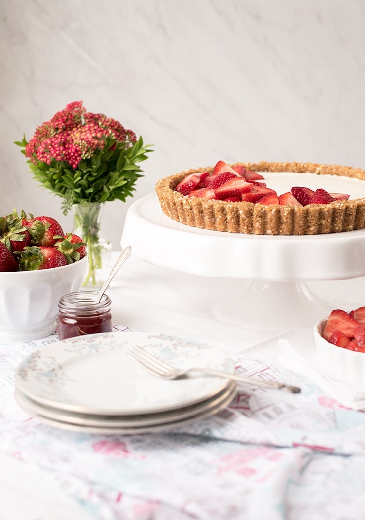 table scene with strawberry tart on cake pedestal