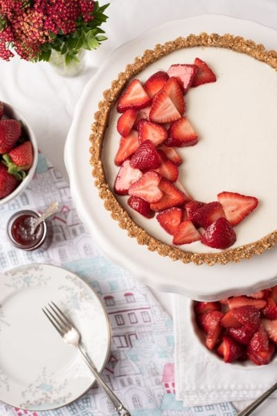 panna cotta tart topped with strawberries on a white plate next to bowls of strawberries, dessert plates and a vase of flowers