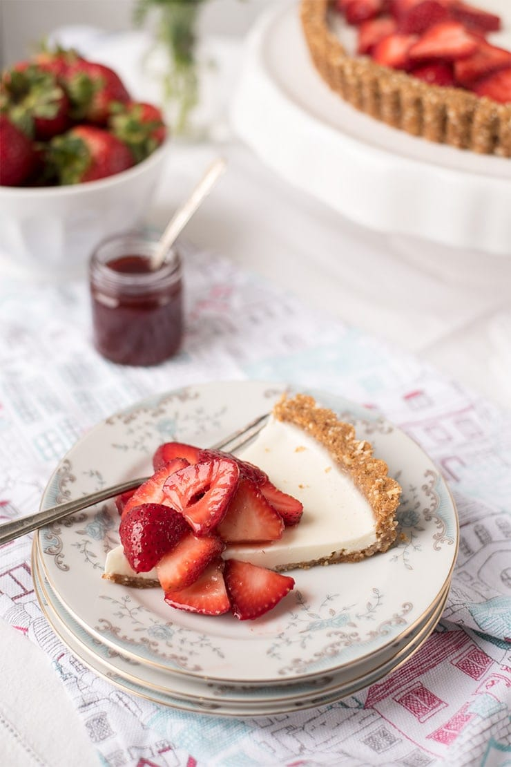 Juicy, sweet strawberries are the star of this icebox dessert. This Strawberry Panna Cotta Tart recipe is a splendid way to highlight the beauty and sweetness of fresh, in-season strawberries which are layered on a creamy gelatin filling and sweet almond, graham cracker crust. #strawberrytart #pannacotta #iceboxdessert #summerdessert #tart #dessertrecipe
