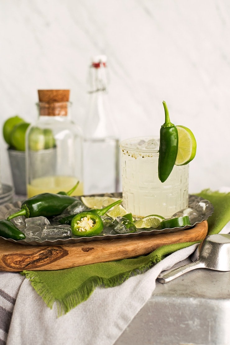 candied jalapeno margarita salt on glass garnished with a lime and fresh jalapeno