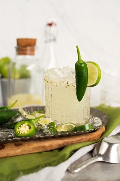 Glass filled with margarita cocktail topped with a whole jalapeno and a slice of lime