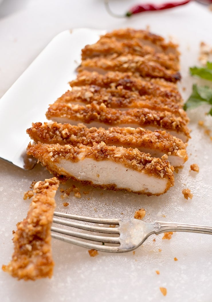 breaded chicken on a cutting board with a fork