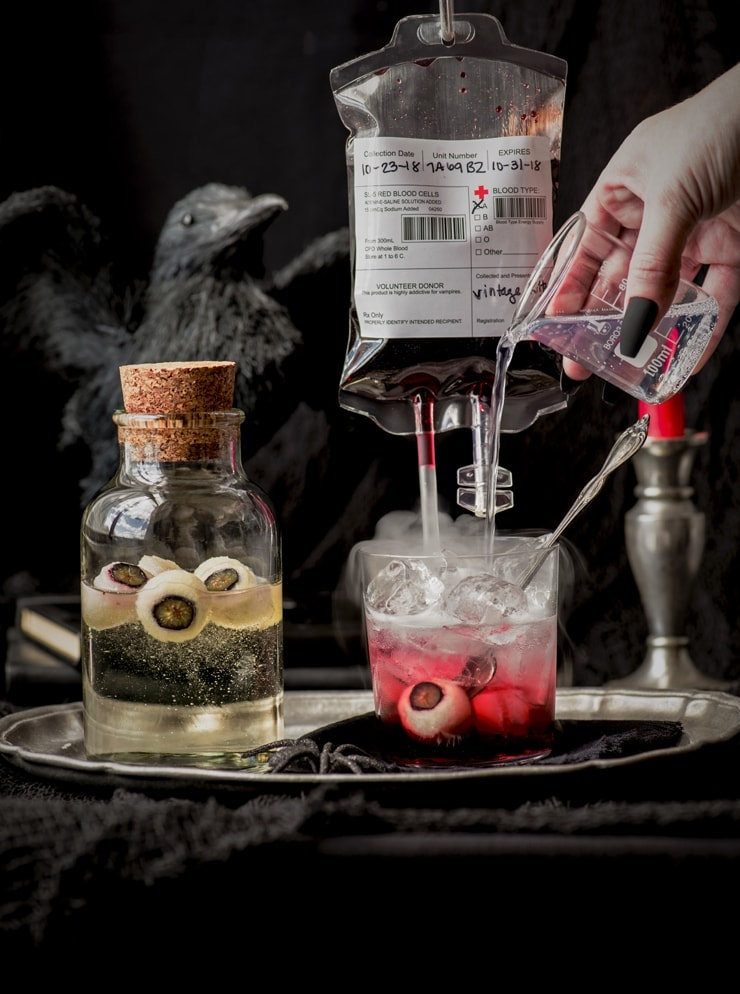 pouring tonic into a glass filled with blood and an eyeball