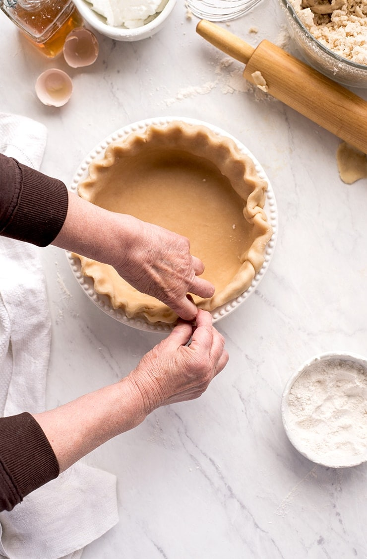 hands pinching a fluted pie crust