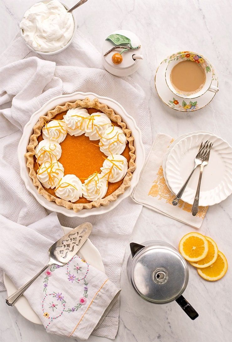 sweet potato pie surrounded by a coffee cup, whipped cream and percolator