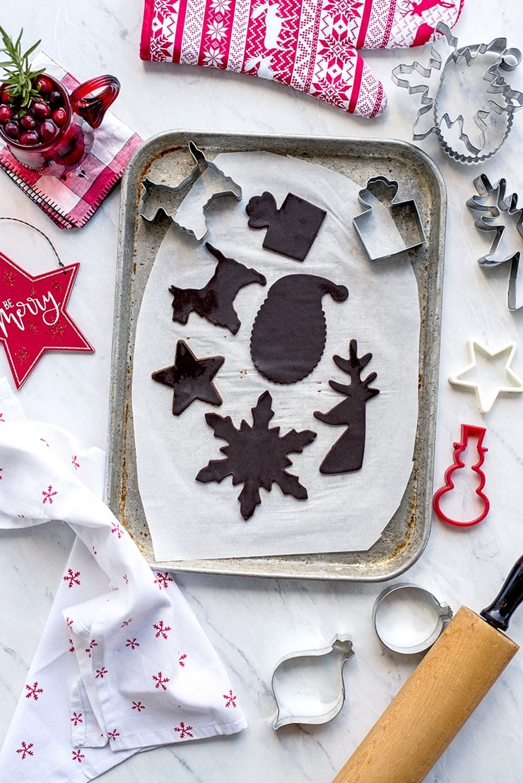 Cut out chocolate gingerbread cookies on a cookie sheet ready for baking
