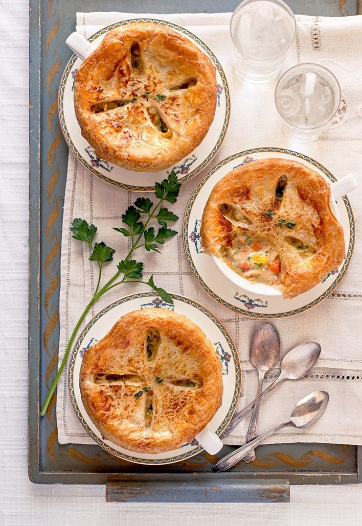 three root vegetable pot pies on a painted wooden tray with spoons and glasses of water