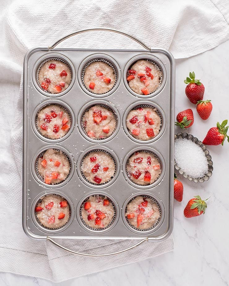 Strawberry muffin batter in muffin tin before baking