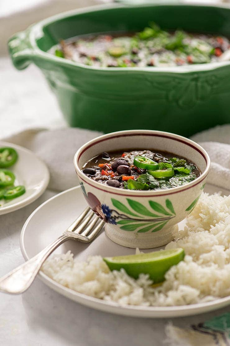Small antique bowl filled with black beans on a plate with rice, a lime and a fork