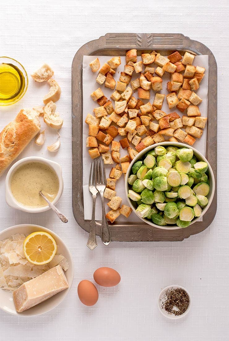 Table set with caesar salad ingredients: croutons, brussels sprouts, parmesan, pepper, eggs, bread, garlic, olive oil and pepper
