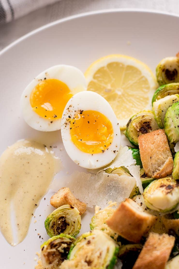 We've updated the classic grilled romaine Caesar salad with charred brussels sprouts. It's topped with a creamy homemade dressing, jammy soft boiled eggs and garlicky croutons.Via @vintagekittycom #brusselssprouts #caesarsalad #salad #dinnerrecipes #vintagekittycom #eggs