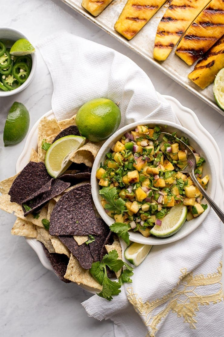 grilled pineapple salsa in a bowl surrounded by limes and tortilla chips