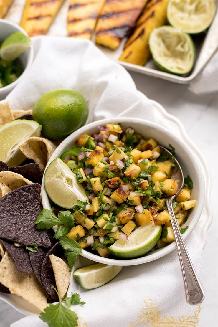 grilled pineapple salsa in a bowl with a spoon and lime wedges