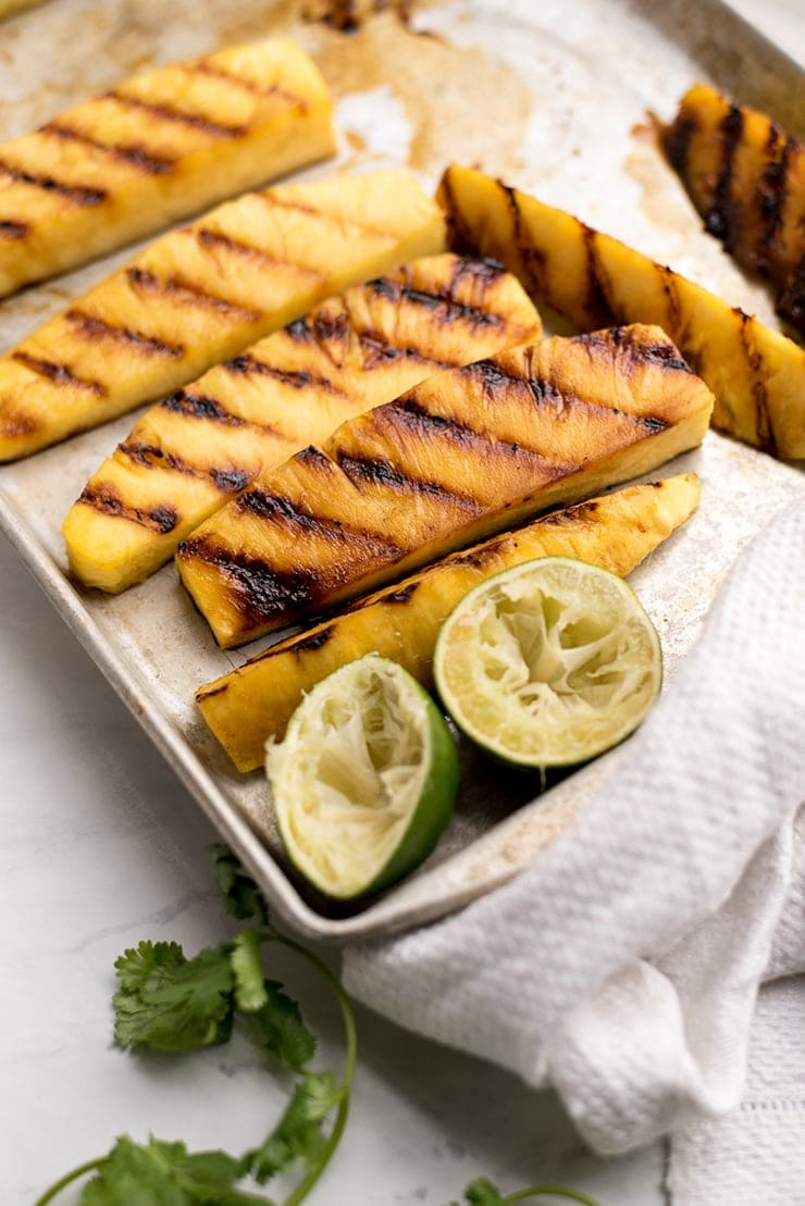tray of grilled pineapple wedges next to squeezed limes